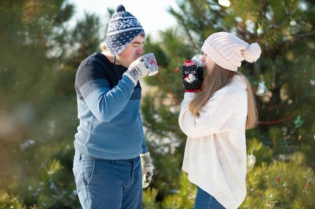Der typ mit dem mädchen geht spazieren und küsst sich im winterwald mit einer tasse heißem getränk. ein gemütlicher winterspaziergang durch den wald mit einem heißen getränk. liebespaar, winterurlaub Premium Fotos