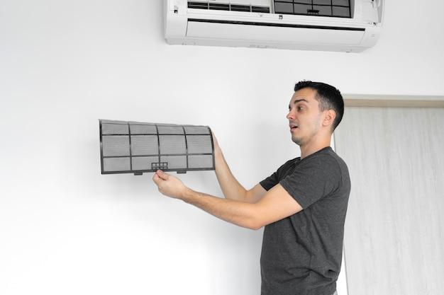 Der typ reinigt den filter der haushaltsklimaanlage von staub. sehr verschmutzter filter der klimaanlage. pflege der klimaanlagen. Premium Fotos
