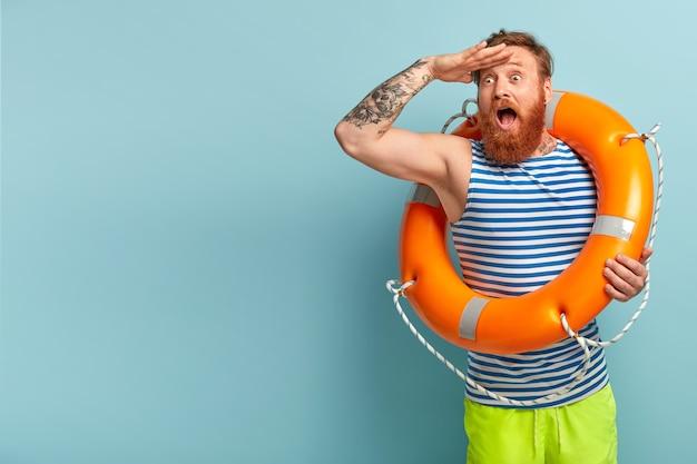 Der überraschte junge urlauber mit roten haaren und bart kommt mit sicherheitsausrüstung an den strand, da er nicht schwimmen kann Kostenlose Fotos