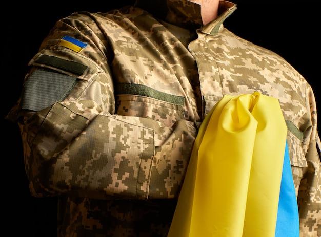 Der ukrainische soldat hält in der hand die gelb-blaue flagge des staates, er drückte seine hand an seine brust Premium Fotos