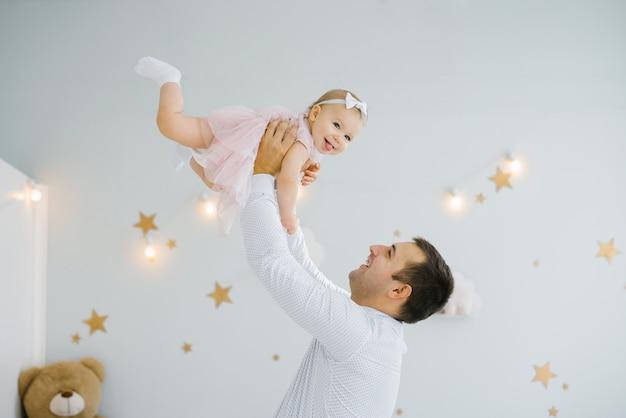 Der vater hält die einjährige tochter in einem rosa kleid auf hohen armen, die tochter lächelt und ist glücklich. Premium Fotos
