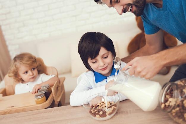 Der vater von zwei jungen beschäftigt sich mit der kindererziehung. Premium Fotos