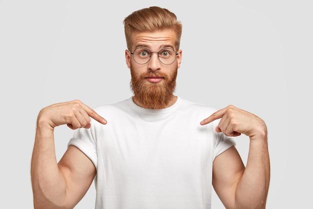 Der verblüffte rothaarige mann hat einen dicken bart, zeigt auf den kopierbereich des t-shirts und zeigt platz für slogan oder logo Kostenlose Fotos