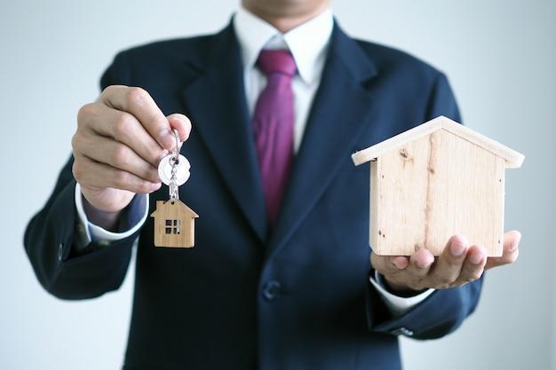 Der verkäufer hält den hausschlüssel. bereiten sie den versand an den neuen hausbesitzer vor. Premium Fotos