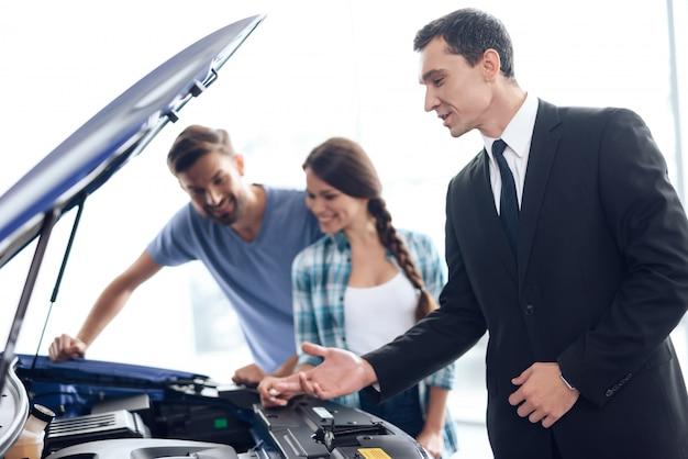 Der verkäufer hilft der jungen familie bei der auswahl des autos. Premium Fotos