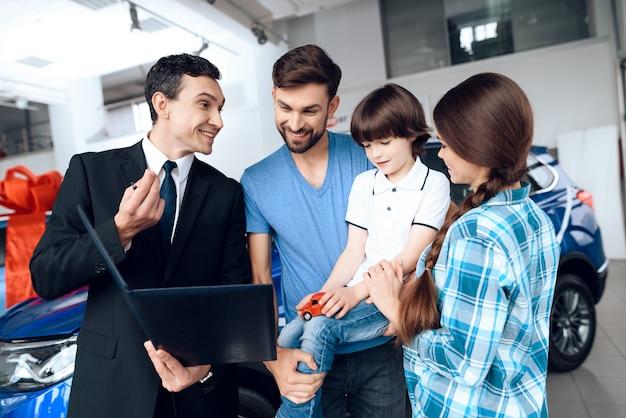 Der verkäufer zeigt der familie die auswahl der autos. Premium Fotos