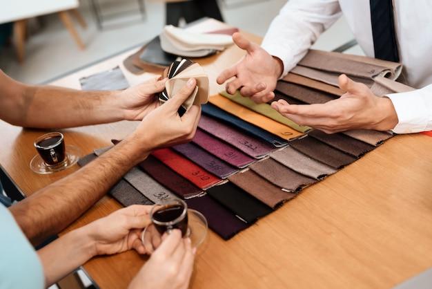 Der verkäufer zeigt materialmuster für möbel. Premium Fotos