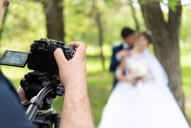 Der videofilmer fotografiert die eheleute im sommer im garten. Premium Fotos