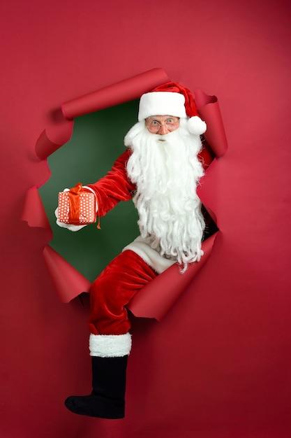 Der weihnachtsmann hält die geschenkbox in der hand durch ein papierloch. Premium Fotos