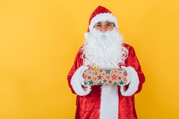 Der weihnachtsmann hält ein geschenk auf gelb Premium Fotos
