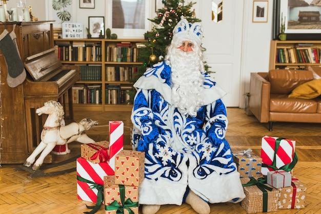 Der weihnachtsmann in einem blauen pelzmantel sitzt im weihnachtsinnenraum vor dem hintergrund Premium Fotos