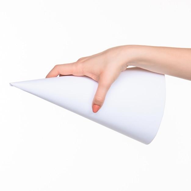 Der weiße kegel der requisiten in den weiblichen händen auf weißem hintergrund mit rechtem schatten Kostenlose Fotos