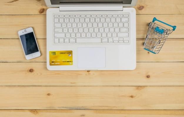 Der weiße laptop mit intelligentem telefon, kreditkarte und dem einkaufslaufkatzenmodell auf dem holztisch. e-commerce einkaufen. Premium Fotos