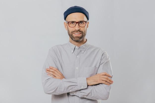 Der zufriedene, selbstbewusste, männliche designer trägt eine stilvolle kopfbedeckung in einem weißen hemd und verschränkt die arme Premium Fotos