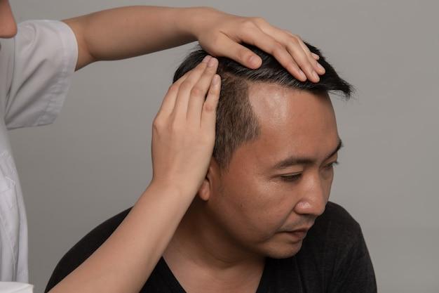 Dermatologe, der das haar des patienten überprüft das asiatische manngrauhaarsorgen-haarausfallproblem auf gesundheitswesenshampookonzept. Premium Fotos