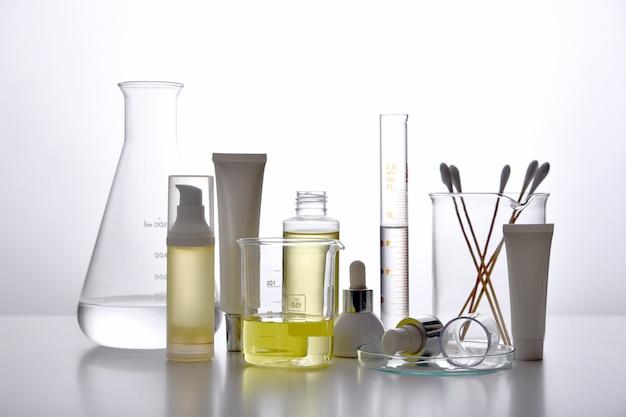 Dermatologe formuliert und mischt pharmazeutische hautpflege, kosmetische flaschenbehälter und wissenschaftliche glaswaren. erforscht und entwickelt das konzept für schönheitsprodukte. Premium Fotos