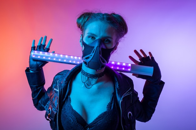Design art konzept. kreatives buntes helles neonporträt. . filmisches nachtporträt der frau in der schutzmaske hält lampe Premium Fotos
