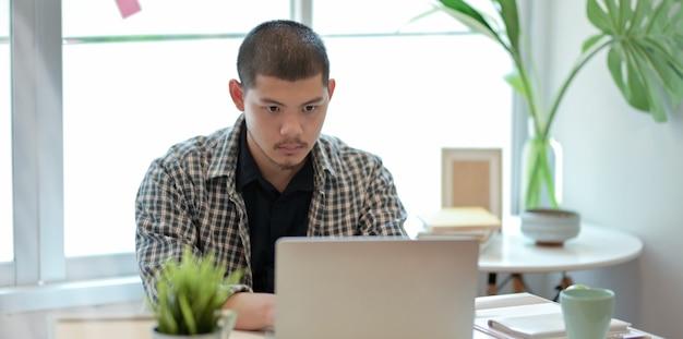 Designer, der an seinem projekt bei der anwendung des laptops arbeitet Premium Fotos