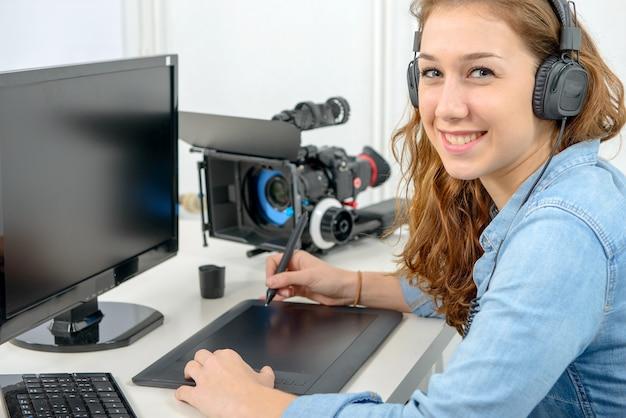 Designer der jungen frau, der grafiktablett für die videobearbeitung verwendet Premium Fotos