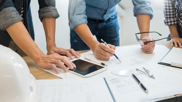 Designer im büro arbeiten diskussion blueprint architect an einem neuen projekt design draw teamwork auf schreibtisch aus holz. Premium Fotos