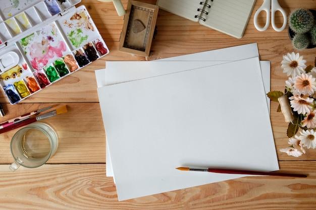 Designer- oder artist-schreibtisch mit aquarell, pinsel, stiften und farben. Premium Fotos