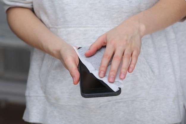 Desinfektionstelefon der frau mit antiseptischem feuchttuch. antiseptische serviette zur verhinderung der ausbreitung von keimen, bakterien und coronaviren. coronavirus prävention. verhindern sie krankheit coronavirus nach öffentlichen platz. Premium Fotos