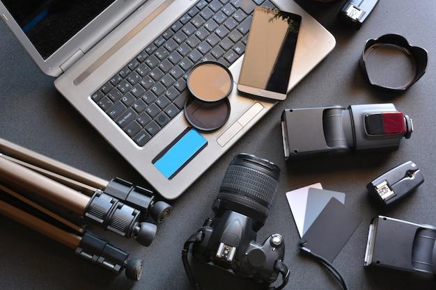 Desktop mit fotoausrüstung, kamera, stativ, blitz und computer Premium Fotos