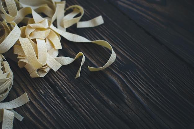 Detail von teigwarenbandnudeln auf einem hölzernen hintergrund Kostenlose Fotos