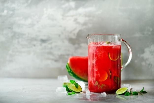 Detoxwasser mit wassermelone, kalk, minze und eis, kopienraum Premium Fotos