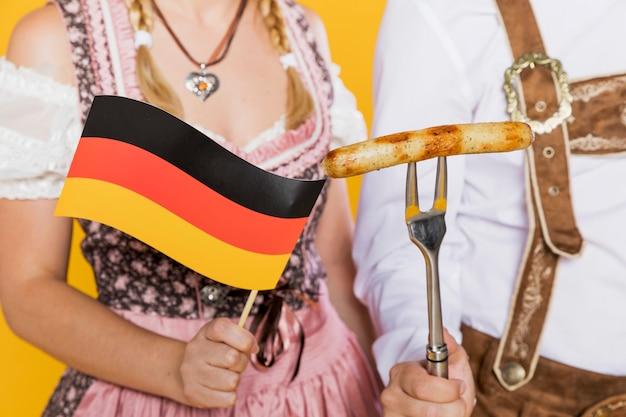 Deutsche flagge des jungen mannes und der frau und gegrillte wurst Kostenlose Fotos