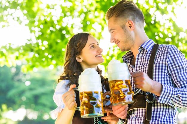 Deutsche paare in trinkendem bier tracht Premium Fotos