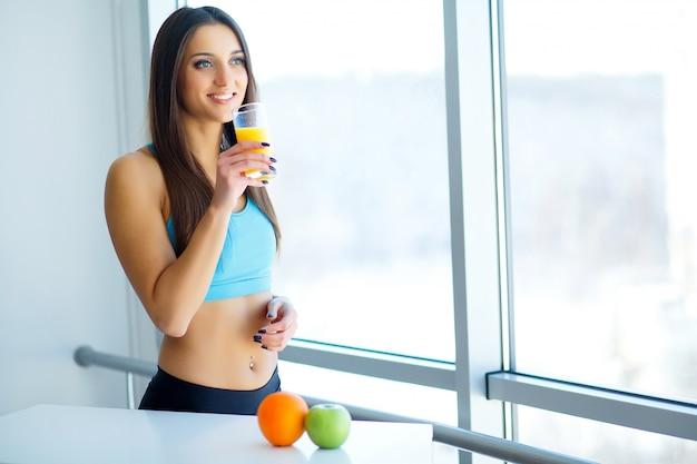 Diät. nahaufnahme auf der jungen frau der eignung, die orange smoothie in der küche trinkt Premium Fotos