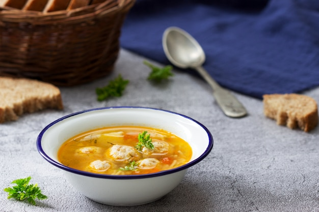 Diät-suppe mit fleischbällchen, kartoffeln und nudeln, serviert mit roggenbrot mit kleie. kindermenü. Premium Fotos