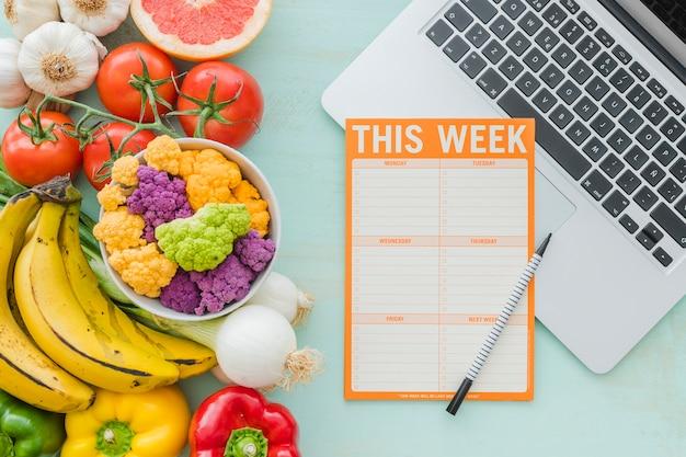 Diät-wochenplan und gesundes gemüse auf hintergrund Kostenlose Fotos