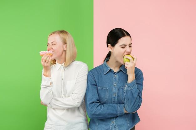 Diätkonzept. gesundes nützliches essen. schöne junge frauen, die zwischen früchten und ungesundem kuchen im studio wählen. menschliche emotionen und vergleichskonzepte Kostenlose Fotos