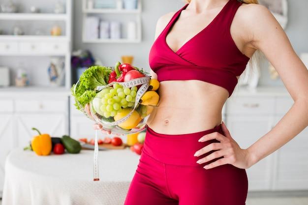 Diätkonzept mit sportlicher frau in der küche Kostenlose Fotos