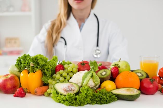 Diätkonzept mit weiblichem wissenschaftler und gesundem lebensmittel Kostenlose Fotos