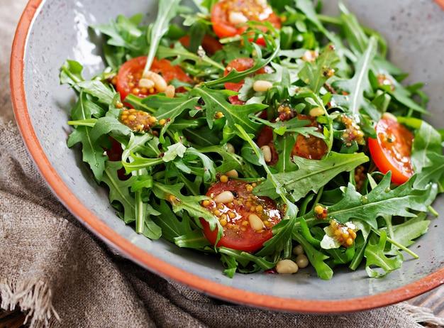 Diätmenü. vegane küche. gesunder salat mit rucola, tomaten und pinienkernen. Kostenlose Fotos