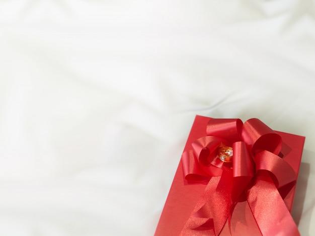 Diamant-hochzeits-ring auf geschenkbox-rot-band Premium Fotos