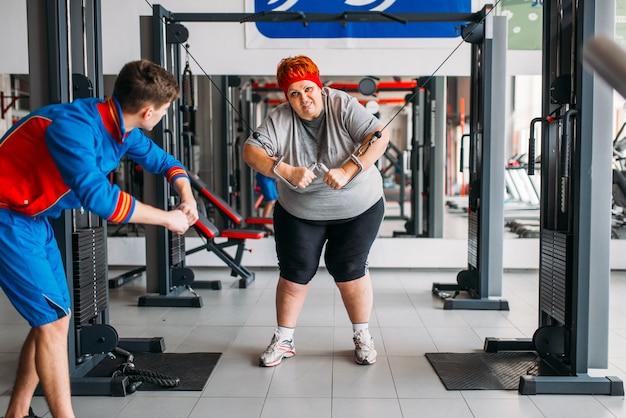 Dicke frau mit übungsmaschine, training mit ausbilder, hartes training im fitnessstudio. kalorienverbrennung, fettleibige weibliche person im sportverein, fettverbrennung Premium Fotos