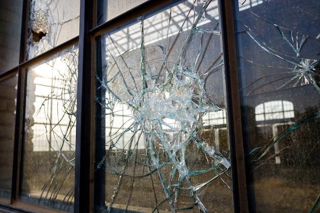Dickes zerbrochenes glas eines fensters in einem verlassenen industriegebiet. Premium Fotos