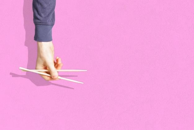 Die abstrakte hand, die das leere paar hölzerne essstäbchen hält, lokalisiert auf farbigem hintergrund, Premium Fotos