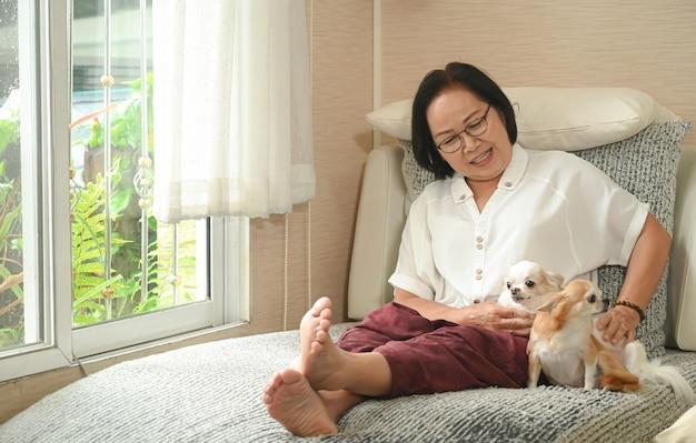 Die ältere asiatische frau, die mit einem hund auf dem sofa sitzt, ruhte sie und lächelte. Premium Fotos