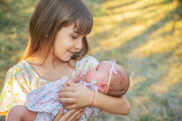 Die ältere schwester hält das neugeborene in den armen. selektiver fokus. menschen. Premium Fotos