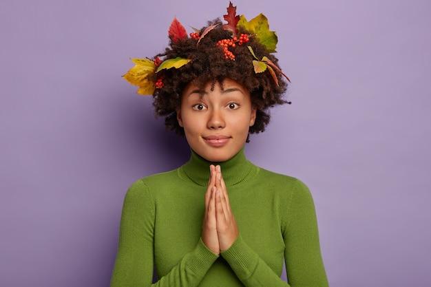 Die afroamerikanische frau hält die handflächen zusammen, betet aufrichtig, hat herbstlaub im haar und trägt einen grünen pullover Kostenlose Fotos