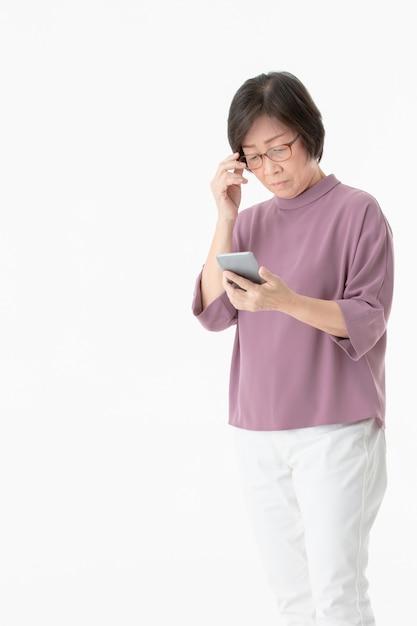 Die alte asiatin, die zum schirm des smartphone und des aussehens schaut, fühlen sich verwirrt und sorgen sich. Premium Fotos