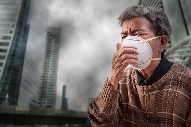Die alte frau, die eine schablone trägt, fürchten problemluftverschmutzung in der stadt Premium Fotos