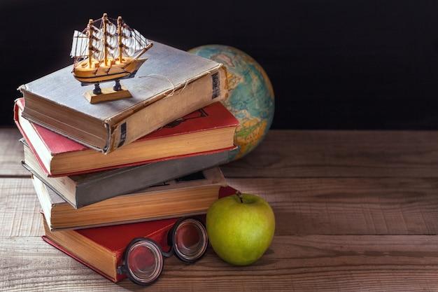 Die alten schulbücher, lehrbücher und schulbedarf liegen auf holztisch. Premium Fotos