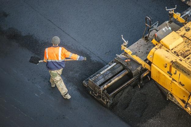 Die arbeiter verlegen eine neue asphaltschicht mit heißem bitumen. arbeit von schweren maschinen und fertiger. ansicht von oben Premium Fotos