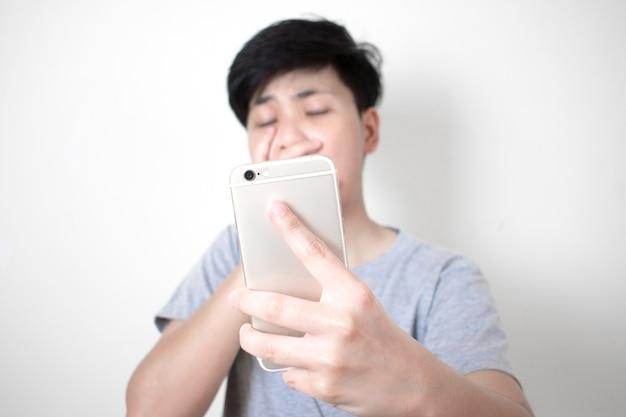Die asiaten tragen ein graues t-shirt, das beim betrachten der nachricht auf dem smartphone schockiert ist. Premium Fotos